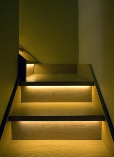 Удобное оформление лестницы светодиодной лентой установленной под бортиками ступеней.